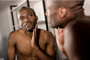 Man touching the smooth skin on his face