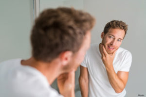 Man looking at his great skin in the mirror